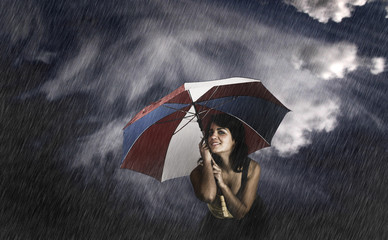 Portrait of a young happy woman posing with a umbrella