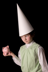Sad young boy in a dunce cap