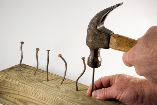 Hands holding hammer with bent nails exasperated