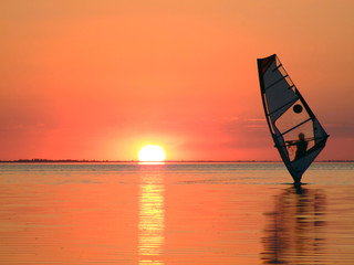 Silhouette of a windsurfer on waves of a gulf on a sunset 3