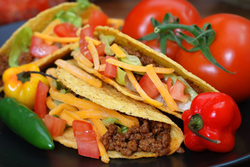 Tacos on plate with tomatoes, habanero and serano peppers.