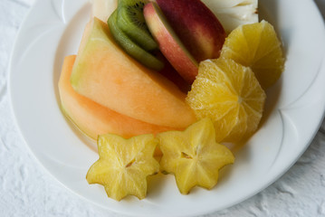 white plate with selection of sliced tropical fruits