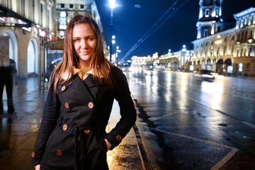 Beautiful young woman standing on illuminated street at night.
