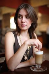 Beautiful young woman enjoying latte coffee in cafe.