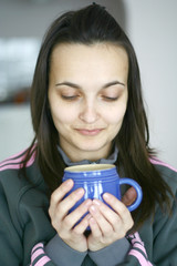 An attractive female having a cup of coffee or tea