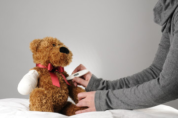 an injured teddy bear having a examination by a pediatrician