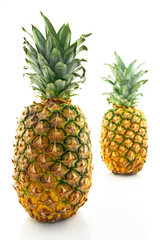 Two ripe pineapples, focus on the closest one.