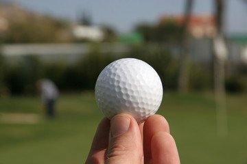 A golf ball in the hand of a golfer