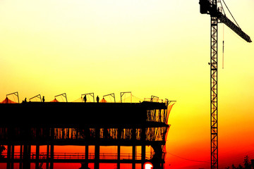 Workers on a construcion site at sunset