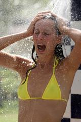Frau in bikini unter der kalten Dusche in der Sonne