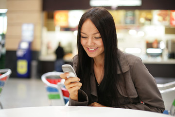 Beautiful young woman smiling looking at mobile phone