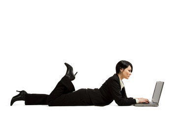 A businesswoman lying down on the floor typing on her laptop