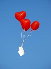 Rote herzförmige Luftballons mit Postkarte, blauer Himmel