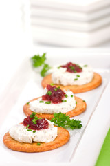 Three crackers with goat cheese and cranberry orange sauce