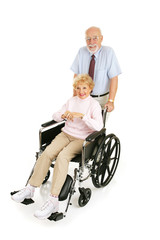 Senior man pushing his wife in wheelchair.  Full body isolated