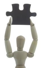 Manikin holds black puzzle piece high up