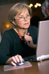 Mature woman using a laptop computer, portrait