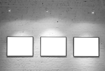 three frames on brick white wall