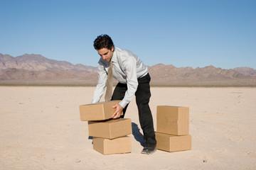 Businessman organizing cardboard shipping boxes