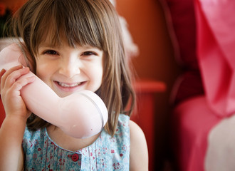 Happy young girl playing with a big pink phone