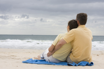 Sitzendes Paar Arm in Arm am Strand
