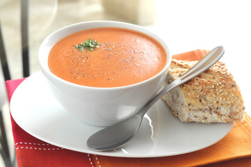 Hot tomato soup served with crusty bread.