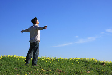 Young man looking to the sky with his arms outstretched..