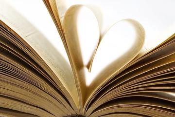 Pages of a book folded in to a heart shape isolated on white