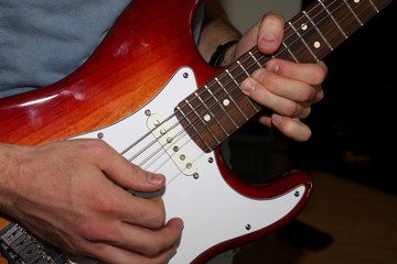 Man's hands playing an electric guitar, strings bending