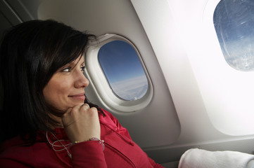 young woman is on passanger seat at airplane