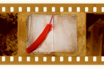 old 35mm frame photo with vintage book and feather