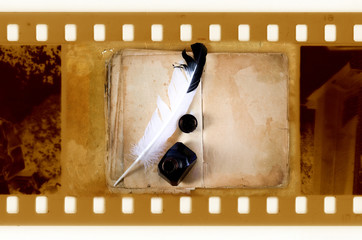 old 35mm frame photo with vintage book inkwell and feather