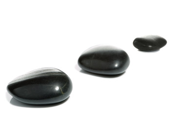 High key shot of three black pebbles on a white surface.