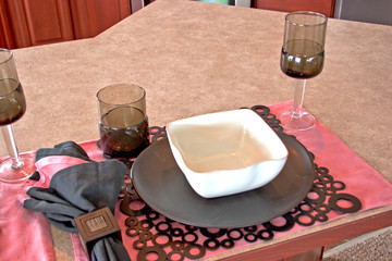 A place setting with a bowl, plate, and glasses.