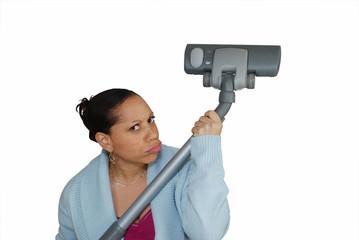 femme tenant un aspirateur comme un fusil