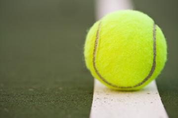 A closeup shot of a tennis ball in a tennis court