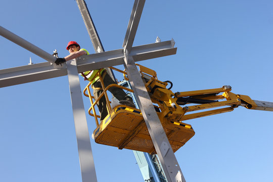 Steel worker on a cherry-picker