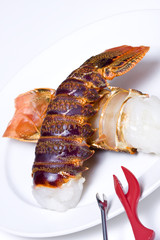 Two uncooked lobster tails on a white plate with picks