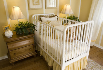 Baby bedroom with crib, pillows and a teddy bear.