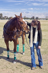 Woman speaks to polo horse