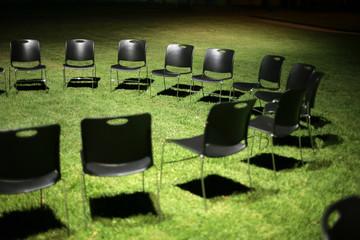Circle of black chears on green grass at night. Shallow DOF.