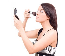 gorgeous woman applying makeup with brush looking into a mirror