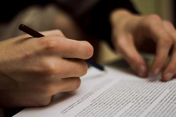 mains en train d'écrire et de signer sur une feuille de contrat