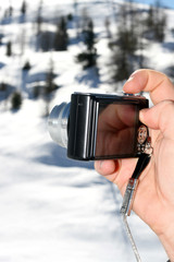 Photo camera in hand on winter background