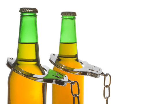 Drunk driving concept - bottled beer and handcuffs.