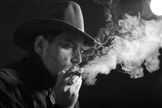 An black and white image of a smoking man