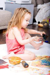 Little girl playing with colorful paints