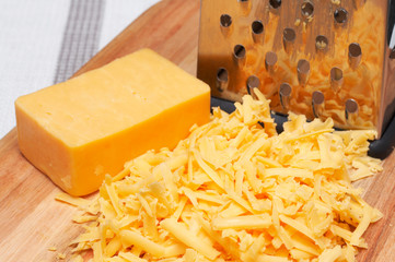 Grated cheddar cheese on wooden board with grater