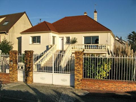 Maison de banlieue blanche au toit rouge avec grille.
