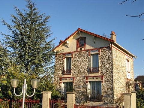 Maison de banlieue en pierre avec grand sapin. France.